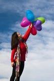 La fille mignonne retenant un groupe de coeur monte en ballon sur le fond bleu de ski Photo libre de droits