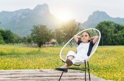 La fille mignonne s'asseyent et détendent sur la chaise et le fond jaune de fleur photographie stock