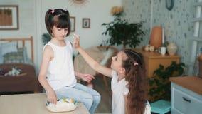 La fille mignonne tache le visage de soeur avec de la farine, ont le temps d'amusement à la cuisine, mouvement lent banque de vidéos