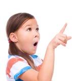 La fille mignonne tient son visage dans l'étonnement Photographie stock libre de droits