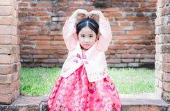 La fille mignonne utilisant des costumes de la Corée montrent la main de symbole d'amour Photo libre de droits