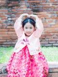 La fille mignonne utilisant des costumes de la Corée montrent la main de symbole d'amour Image stock