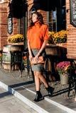 La fille mince élégante habillée dans la jupe grise, chemisier orange tenant le petit sac orange marche dans la rue un jour ensol photo libre de droits