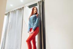 La fille mince avec des redheads choisit des vêtements femme dans le pantalon en cuir rouge posant dans la vue inférieure de cabi images stock