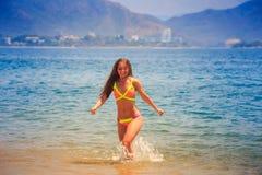 la fille mince blonde dans des courses de bikini hors de l'eau de mer azurée sourit Images stock