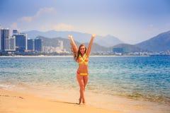 La fille mince blonde dans le bikini pose sur l'orteil d'astuce sur la plage Image libre de droits