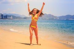 La fille mince blonde dans le bikini pose sur l'orteil d'astuce sur la plage de sable Image libre de droits