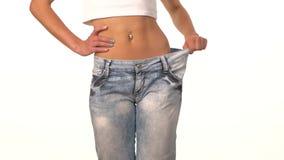 La fille mince dans de grands jeans, la montrant perdent le poids banque de vidéos