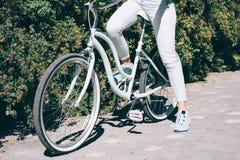 La fille mince dans des jeans s'assied sur sa bicyclette de ville en parc Images stock