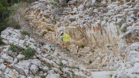 La fille mince habillée dans le maillot de bain vert blanc et le grand chapeau marche au-dessus des étapes près de hautes roches  banque de vidéos