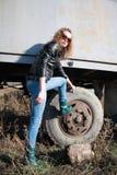 La fille a mis un pied sur une roue Image libre de droits