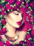 La fille modèle de beauté avec les roses roses fleurissent la guirlande et le maquillage de mode Photographie stock libre de droits
