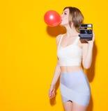 La fille moderne à la mode posant dans le dessus et la jupe colorés gonfle la bulle rouge du chewing-gum et avec un appareil-phot images stock