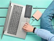 La fille moderne s'assied sur un plancher en bois bleu et utilise un ordinateur portable Génération Z Le concept de travailler en Image libre de droits