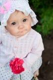 La fille 8 mois de petit bébé ukrainien européen sur une promenade dans le jardin tient une fleur et des fraises dans des ses mai photo libre de droits