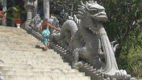 La fille monte les escaliers escalier décoré des statues des dragons banque de vidéos