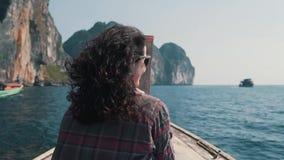 La fille monte un bateau aux roches dans l'océan banque de vidéos