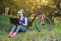 la fille monte un cycliste après un voyage à la forêt de pin et fait un autre itinéraire sur l'ordinateur portable Photos libres de droits