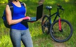 la fille monte un cycliste après un voyage à la forêt de pin et fait un autre itinéraire sur l'ordinateur portable Images stock