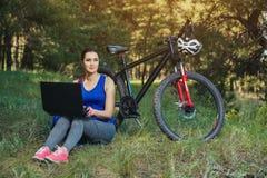 La fille monte un cycliste après un voyage à la forêt de pin et fait un autre itinéraire Photos stock