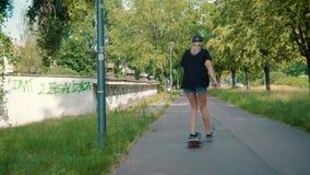 La fille monte une planche à roulettes sur la rue en parc d'été banque de vidéos