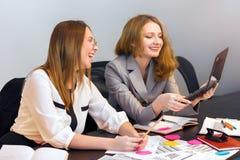 La fille montre l'information de collègue sur l'écran d'ordinateur portable Image libre de droits