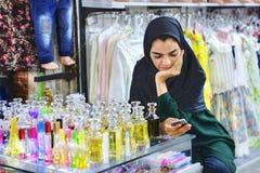 La fille musulmane iranienne vend l'eau de toilette, Chiraz, Iran Photos stock