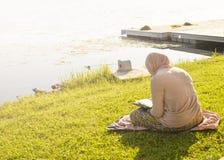 La fille musulmane s'assied sur l'herbe devant le lac et lit livre sacré image libre de droits