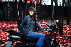 La fille mystérieuse sur une moto rouge Photographie stock