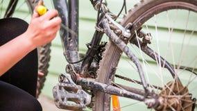 La fille nettoie le vélo avec un tournevis banque de vidéos