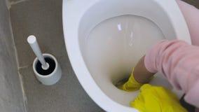La fille nettoie soigneusement la toilette dans les gants en caoutchouc avec une éponge clips vidéos