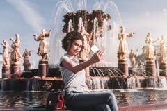 La fille noire se photographie devant une fontaine Photo libre de droits