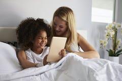 La fille noire tient la tablette, dans le lit avec la maman caucasienne photos stock