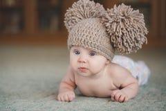 La fille nouveau-née dans un chapeau, se trouvant sur le plancher Images stock