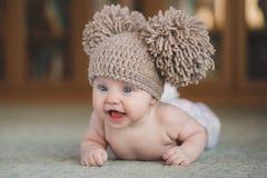 La fille nouveau-née dans un chapeau, se trouvant sur le plancher Image stock