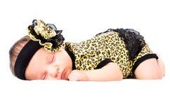 La fille nouveau-née de sommeil mignonne dans un léopard vêtx Image libre de droits