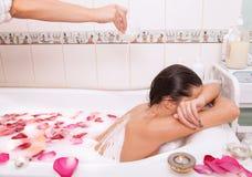 La fille nue attirante apprécie un bain avec du lait et les pétales roses photographie stock libre de droits