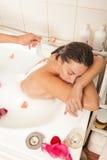 La fille nue attirante apprécie un bain avec du lait et les pétales roses photographie stock