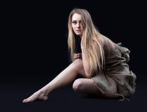 La fille nue en toile de jute s'asseyent dans l'obscurité Photographie stock libre de droits