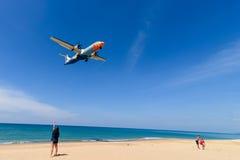 La fille observe l'avion de débarquement d'air de Bangkok à l'aéroport de phuket Image libre de droits