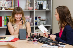 La fille obtient le crayon correcteur sous la direction de l'artiste de maquillage Photo libre de droits