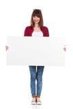 La fille occasionnelle pose avec l'affiche vide blanche Photos stock
