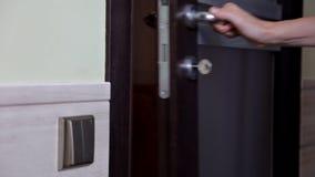 La fille ouvre et ferme la porte à l'appartement La personne employant la clé et fermant à clef la porte de l'appartement clips vidéos