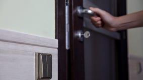 La fille ouvre et ferme la porte à l'appartement La personne employant la clé et fermant à clef la porte de l'appartement banque de vidéos