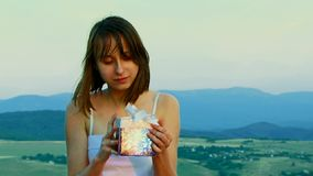 La fille ouvre un cadeau banque de vidéos