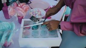 La fille ouvre une boîte avec un couteau avec les gâteaux bleus banque de vidéos