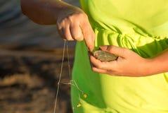 La fille a pêché les poissons sur l'amorce Photo stock