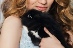La fille parfaite s'assied près de la fenêtre avec un lapin sur ses mains GE images stock