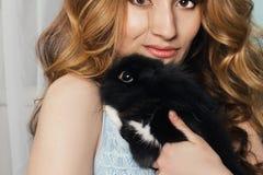 La fille parfaite s'assied près de la fenêtre avec un lapin sur ses mains GE image libre de droits
