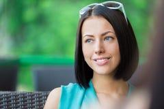 La fille parle avec l'ami s'asseyant au restaurant Image stock